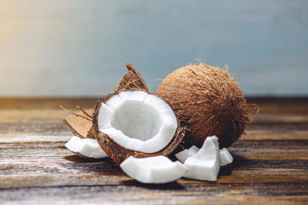 Foto de Open coconut with white pulp on wooden background. Organic healthy dietary vegan product widely used in cosmetics - Imagen libre de derechos