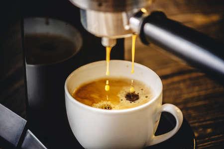Photo pour Espresso pours from the coffee machine into a white Cup forming a Golden foam - image libre de droit