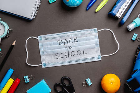 Photo for Stationery school supplies around the medical mask on black background. Top view. Concept of back to school. - Royalty Free Image