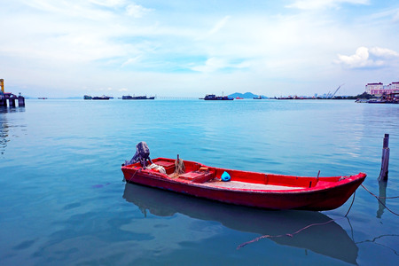 Local red mini boat parked at Jetty clan port with many ships on the deep blue sea in background Georgetown, Panang Malaysia