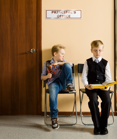 Two schoolboys are sitting next to principal's office. They are twin, but they have different each other behavior and clothes. One model release, because for creating this picture were used two image of one and the same boy.