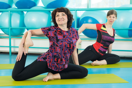 Women doing yoga exercise in the gymの写真素材