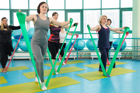 Women doing gym exercises using latex fitness bands