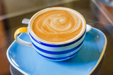 Blue and white cup of latte coffee