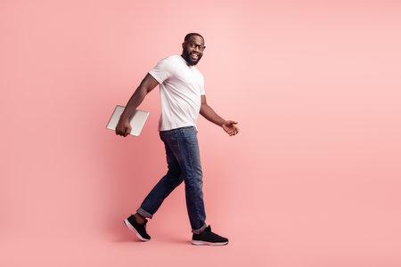 Photo pour Young smiling african man walk carry laptop - image libre de droit