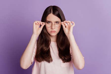 Photo pour Portrait of serious woman in glasses isolated on purple background - image libre de droit
