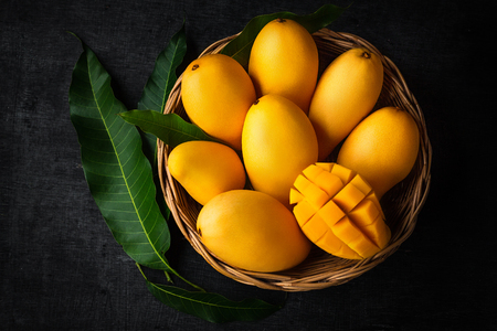 Foto de Yellow Mango Beautiful skin In the basket Blackboard background - Imagen libre de derechos