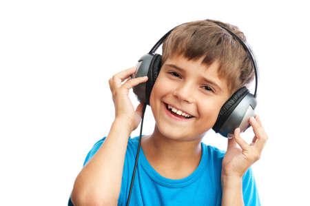 The young boy is laughing and holding headphones