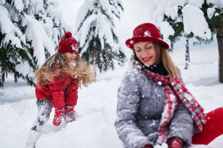 daughter provokes mother play snowballs