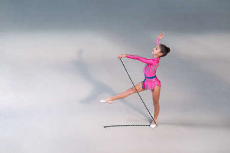 Little girl in pink gymnastic dress doing exercise with gymnastic rope in gym-hall