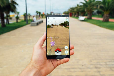 Photo pour BATUMI, GEORGIA- JULY 14, 2016: Hand holding a smartphone to play the game of Augmented Reality Pokemon go - image libre de droit
