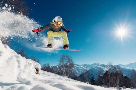 Foto de Girl is jumping with snowboard from the hill - Imagen libre de derechos