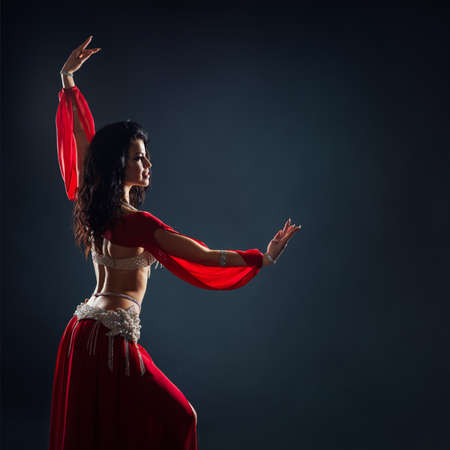 Photo pour beautiful black-haired girl in a red ethnic dress dancing oriental dances in the dark - image libre de droit