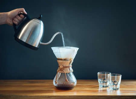 Photo for making coffee by an alternative method, pouring hot water from kettle into a glass decanter on a wooden table and gray background, minimalism side-view - Royalty Free Image