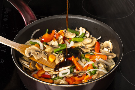 Photo for Adding sauce to fried vegetables with mushrooms in a frying pan on a dark background - Royalty Free Image