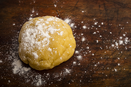 Photo pour ball of dough sprinkled with flour on a wooden cutting board, copy space - image libre de droit