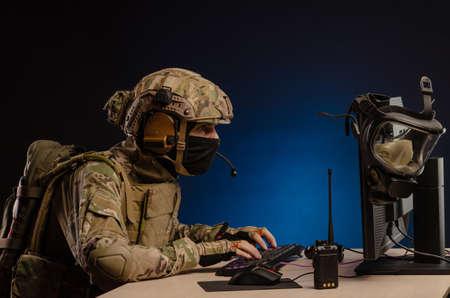 Photo pour military in uniform sitting at a computer conducts cyber warfare - image libre de droit