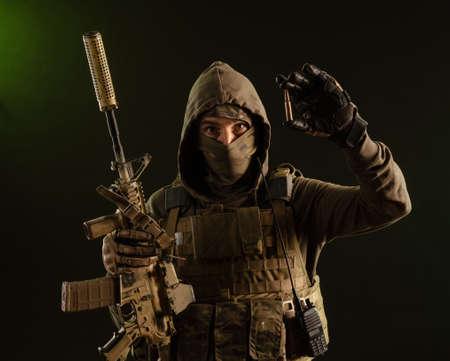 Foto de a soldier-saboteur in military uniform with a weapon on a dark background shows a bullet - Imagen libre de derechos