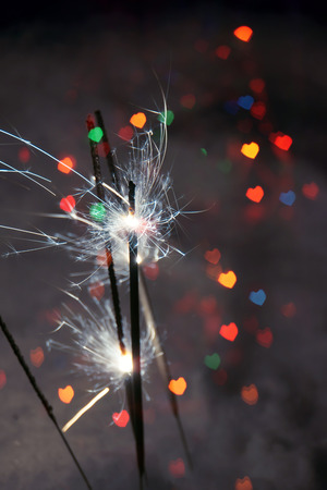 Bengal fire, sparkler and colorful bokeh in a shape of a heart, holiday background.