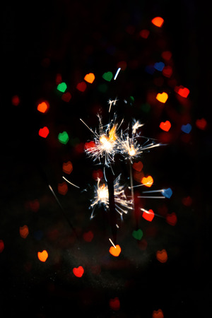 Bengal fire, sparkler and colorful bokeh in a shape of a heart, holiday .