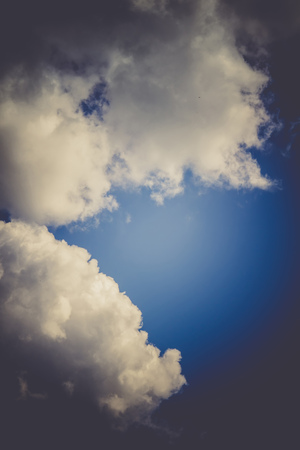 Blue sky with soft dark clouds, natural filtered background.