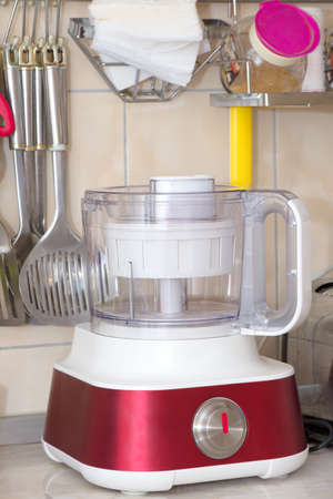 Food processor in the kitchen together with kitchen utensils