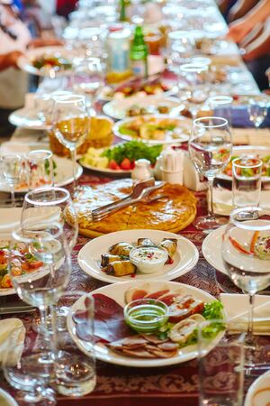 Long Banquet table. Drinks and snacks on the table.  People are sitting at the table. Concept of joint celebrations.
