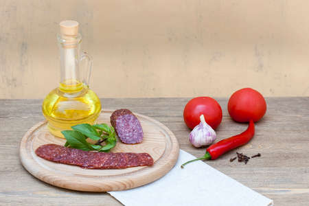 Salami sausage and sunflower oil in the bottles with herbs, tomatoes and spices on wooden table, selective focusの写真素材