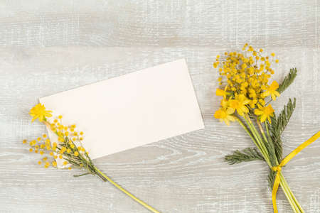 Mimosa and yellow daffodils on a light wooden surface. Yellow orange flowers concept, top view, copy space, postcard for writing on a wooden surface