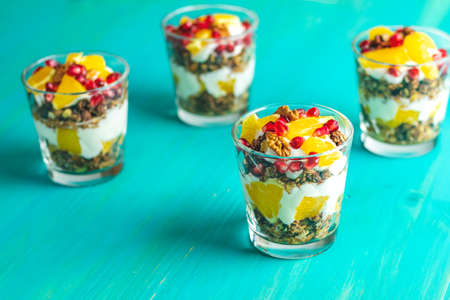 Greek yogurt with granola, orange and pomegranate berries for healthy breakfast on blue turquoise wooden table, copy space, shallow depth of the field.
