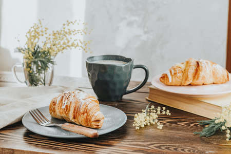 Foto de Continental traditional breakfast with croissants and coffee served on wooden table background empty copy space. French breakfast. - Imagen libre de derechos