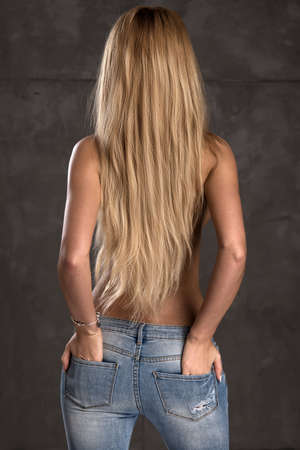 Back side of young woman with straight blonde hair only in jeansの写真素材