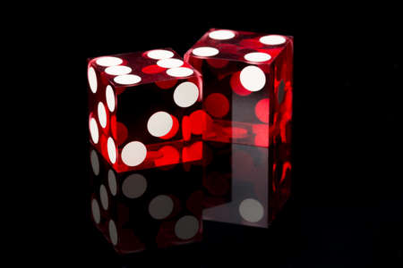 Two red dices on a black background