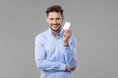Photo pour Handsome man in blue shirt  with white card - image libre de droit