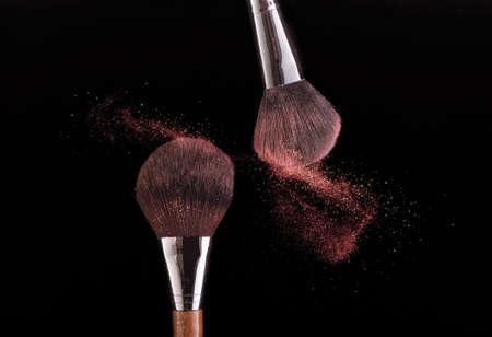 Photo for Two brushes spraying powder on a black background. - Royalty Free Image