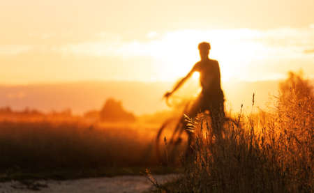 Photo for Cyclist silhouette on a gravel bike stands in a field on a beautiful sunset background. - Royalty Free Image