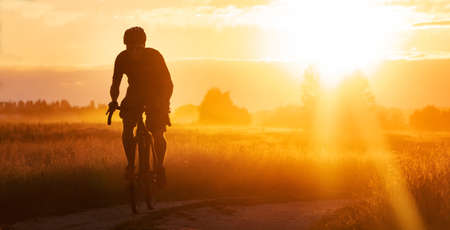 Photo pour Silhouette of a cyclist riding a trail in a field on a dramatic sunset background. - image libre de droit