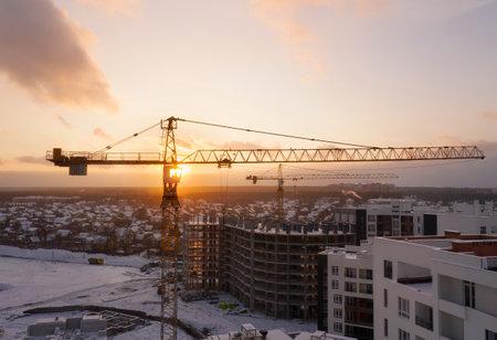 Photo pour Construction site with construction cranes at sunset from aerial view. - image libre de droit