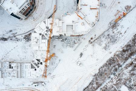 Photo pour Top view of a construction site with cranes covered with snow. Aerial cityscape. - image libre de droit