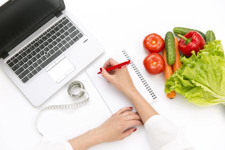 Photo pour Vegetable diet nutrition or medicaments concept. Doctors hands writing diet plan, ripe vegetable composition, laptop and measuring tape on white background - image libre de droit