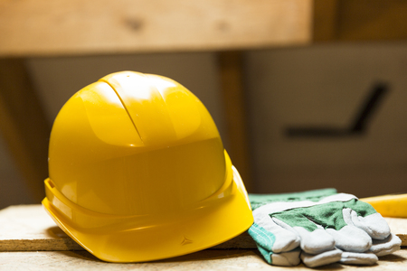 Photo pour Yellow safety helmet and gloves on working surface at attic renovation site - image libre de droit
