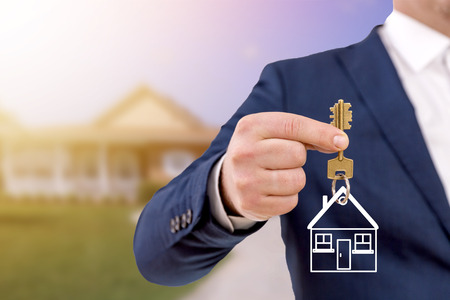 Photo for Real estate agent holding keys in front of a beautiful new home. - Royalty Free Image