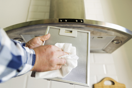 Photo pour Man's hands cleaning aluminum mesh filter for cooker hood. Housework and chores. Kitchen cooker hood on the background - image libre de droit