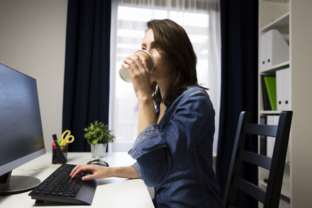 Photo for Beautiful women holding cup of coffee in her hands. Working late concept - Royalty Free Image