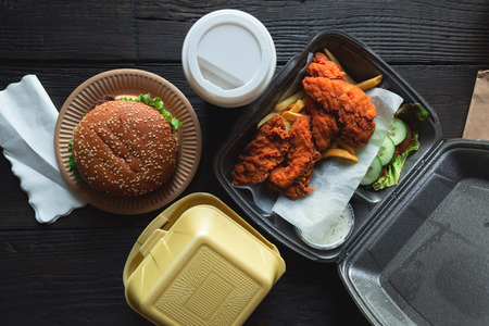 Photo pour Hamburger, french fries and fried chicken in takeaway containers on the wooden background. Food delivery and fast food concept - image libre de droit