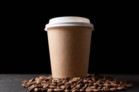 Photo pour Paper cup of coffee and coffee beans on dark wooden table. Good quality coffee - image libre de droit