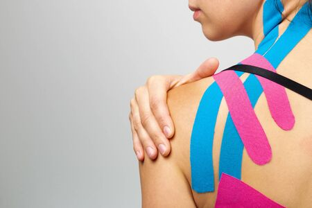 Foto de Kinesiotaping, kinesiology. Female athlete with kinesiotape, muscle tape on shoulder - Imagen libre de derechos