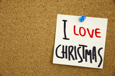 Phrase I LOVE CHRISTMAS in black ext on a sticky note pinned to a cork notice board