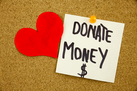 Phrase DONATE MONEY in black ext on a sticky note pinned to a cork notice board