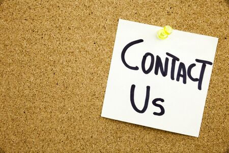Phrase CONTACT US in black ext on a sticky note pinned to a cork notice board